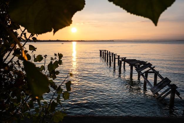 Ein alter baufälliger pier mit zerbrochenen brettern, während eines schönen sonnenuntergangs an einem ruhigen see.