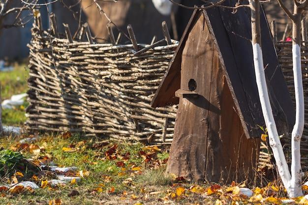 Ein alter bienenstock aus einem baumstamm steht auf dem boden vor dem hintergrund eines weidenzauns