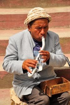 Ein alter mann auf der straße spielt eine hausgemachte flöte