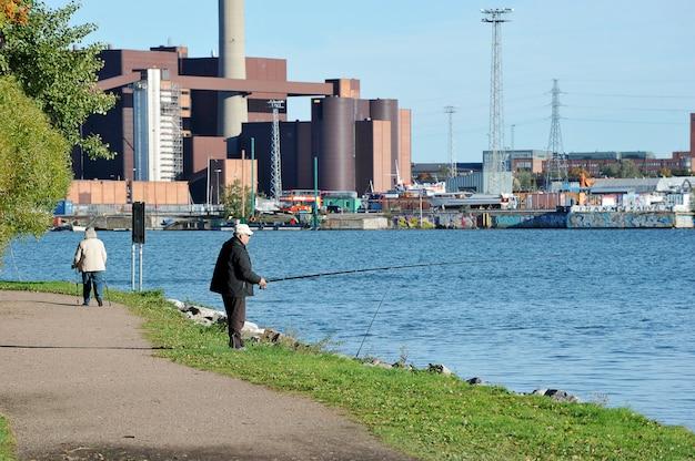 Ein alter mann, der in der mitte von helsinki, finnland fischt