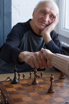 Ein alter mann gibt einem gegner beim schachspiel die hand