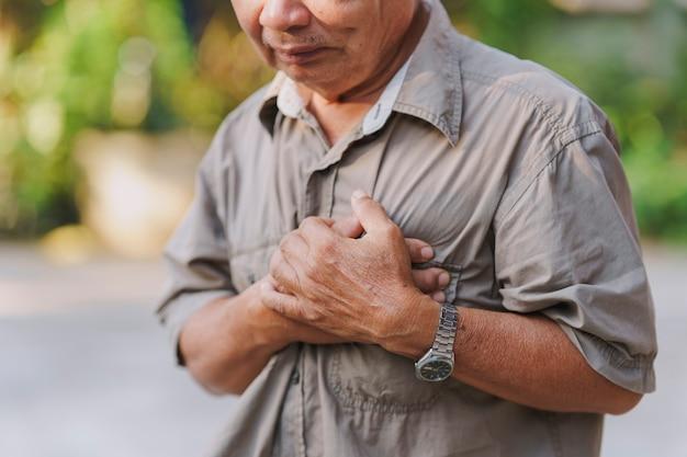 Ein alter mann hält seine brust vor schmerzen konzept der herzkrankheit