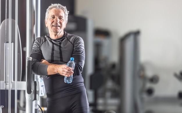 Ein alter mann lehnt sich in einem fitnessstudio mit einer flasche wasser in den händen an ein trainingsgerät.