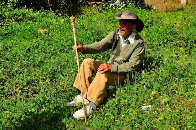 Ein alter mann sitzt auf dem gras und ruht mit einem spazierstock in der hand.