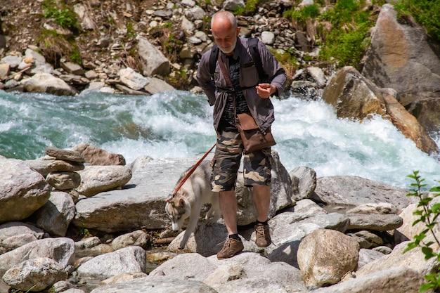 Ein alter mann und ein schlittenhund gehen in der nähe des flusses.