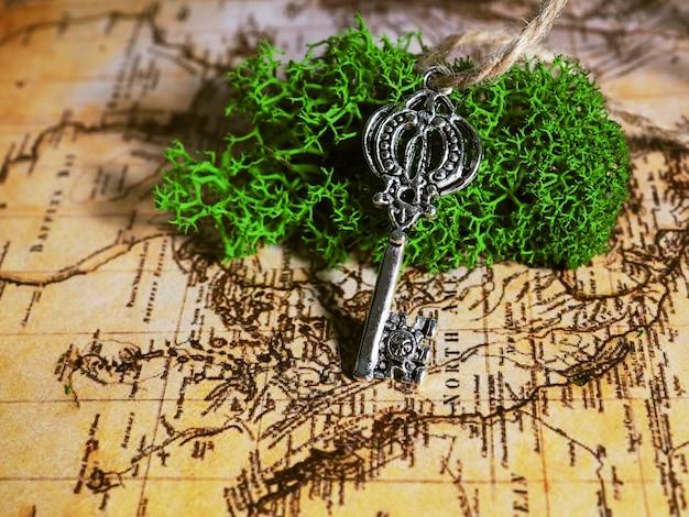 Ein alter schlüssel liegt auf dem moos im hintergrund einer alten karte, der schlüssel zu schatz, reisen und abenteuer.