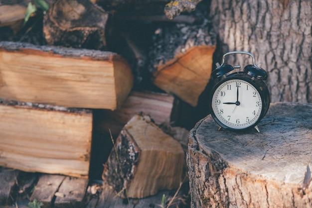 Ein alter wecker um zwölf und ein stern auf einer rustikalen holzoberfläche und brennholz