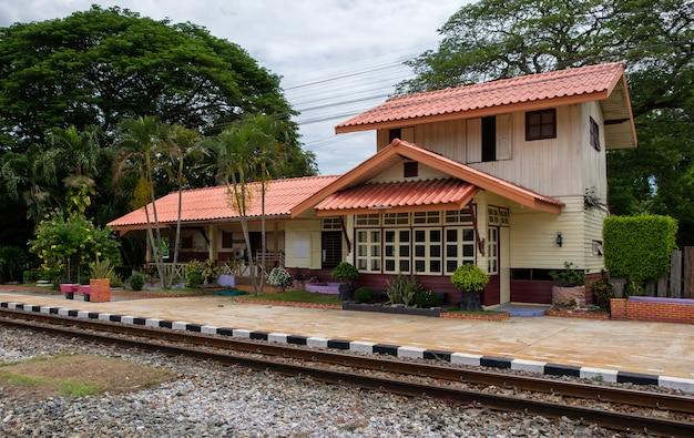 Ein altes bahnhofsgebäude, das nach dem bau eines neuen gebäudes in der landschaft thailands nicht mehr betrieben wurde, vorderansicht mit dem kopierraum.