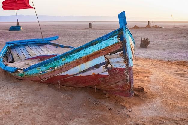 Ein altes boot steht allein inmitten einer salzwüste