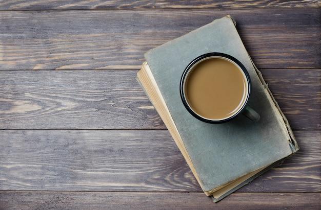 Ein altes buch mit einem zerrissenen einband. kaffee mit milch. holzuntergrund. flache ansicht von oben