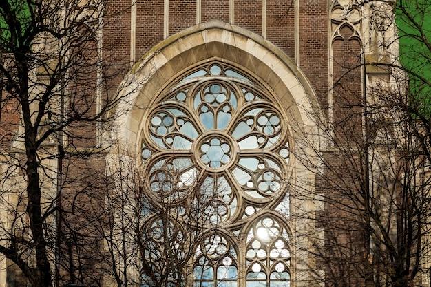 Ein altes eisenfenster mit dekorativen elementen an der fassade einer kirche