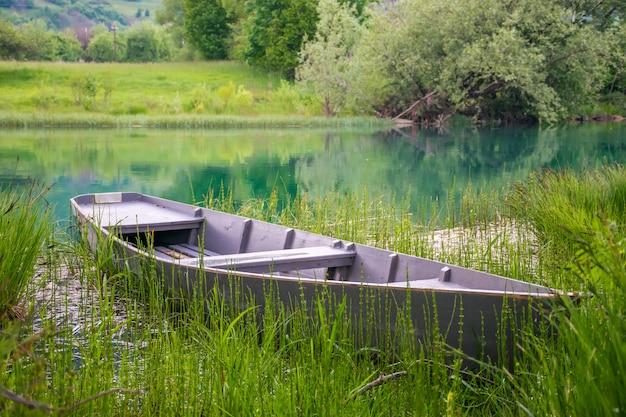 Ein altes fischerboot liegt im schilf am ufer fest.