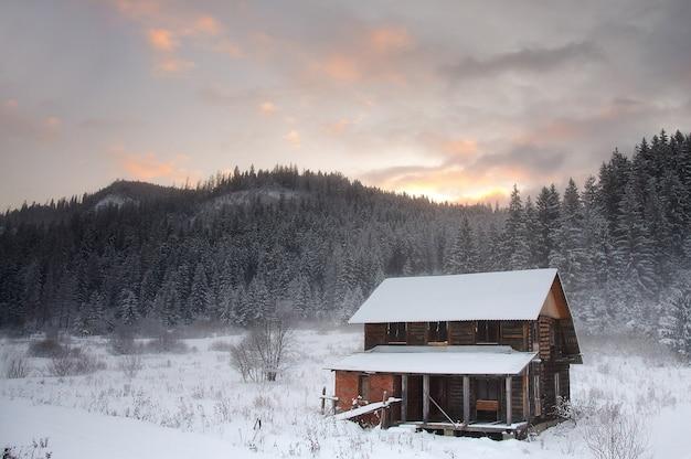 Ein altes hölzernes wohnhaus mit blick auf die karpaten