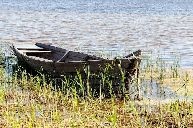 Ein altes holzboot, auf dem man zum angeln auf dem land schwimmen kann