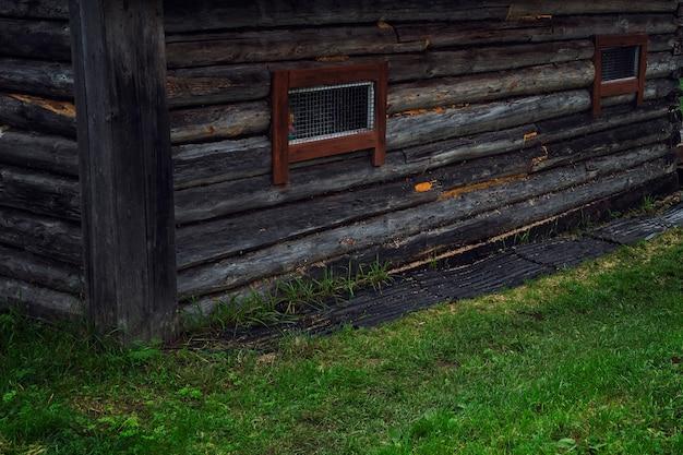 Ein altes holzhaus mit metallstangen an kleinen fenstern. nahaufnahme. heimgefängnis.