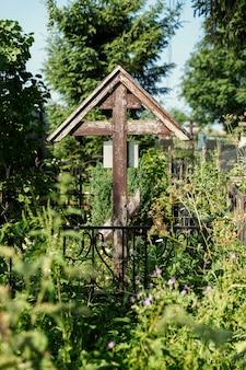Ein altes holzkreuz auf einem überwucherten grab. erinnerung und trauer. vertikal.