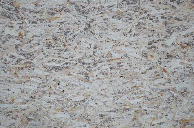 Ein altes orientiertes strangbrett osb, fiberboard hintergrund der beschaffenheit. das blatt besteht aus braunen holzspänen, die zu einem holzfußboden zusammengepresst werden