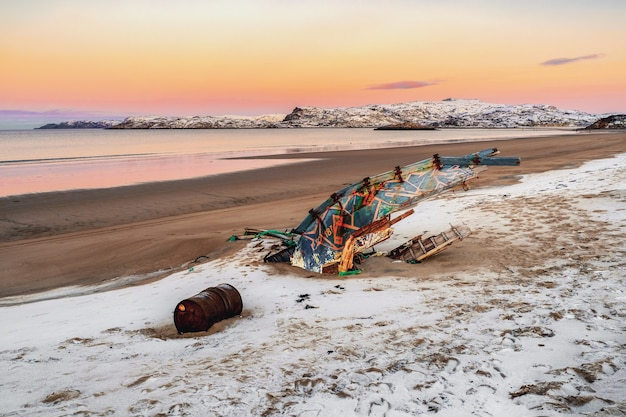Ein altes rostiges fischerboot, das von einem sturm am ufer verlassen wurde. friedhof der schiffe. kola-halbinsel, teriberka, russland.