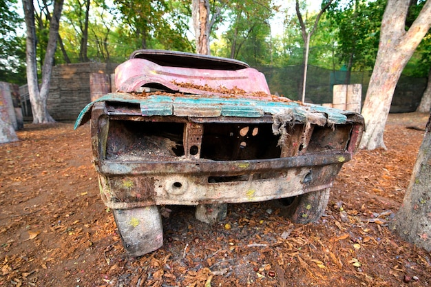 Ein altes rostiges und verlassenes auto auf einer paintball-basis, hinter dem sich spieler verstecken, die vom spiel begeistert sind