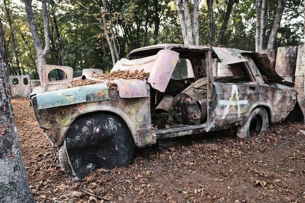 Ein altes rostiges und verlassenes auto auf einer paintballbasis, hinter dem sich vom spiel begeisterte spieler verstecken