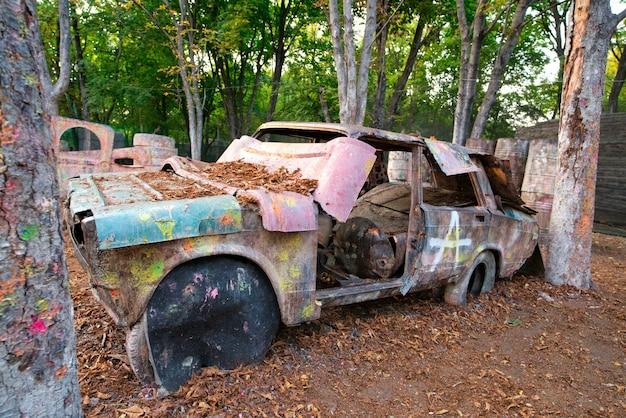 Ein altes rostiges und verlassenes auto auf einer paintballbasis