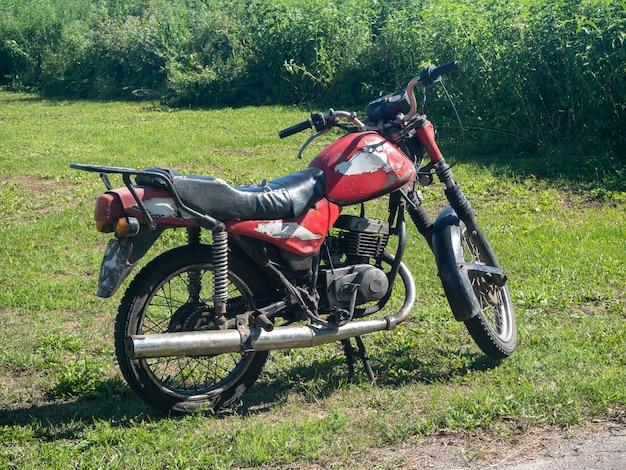 Ein altes rotes motorrad an einem hellen sommertag im dorf
