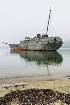 Ein altes sowjetisches walfangboot aus holz, das das schiff am ufer der bucht auf grund lief