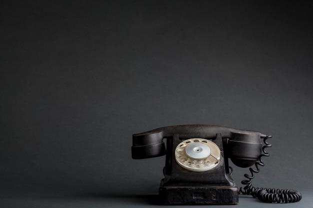 Ein altes telefon auf dem schwarzen hintergrund