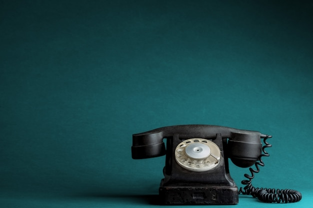 Ein altes telefon auf dem türkisfarbenen hintergrund