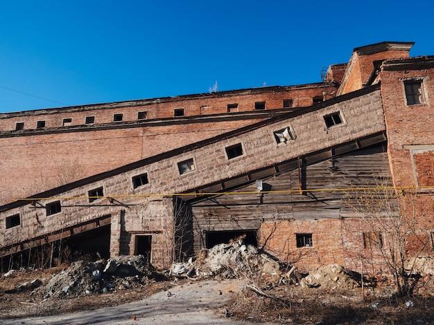 Ein altes verlassenes fabrikgebäude im frühherbst. postapokalyptischer hintergrund. einstürzende gebäude.