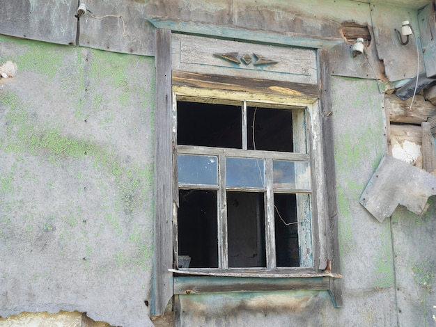 Ein altes zerbrochenes fenster eines hauses im dorf mit glasscherben. verlassenes haus. landschaft. sonniger tag