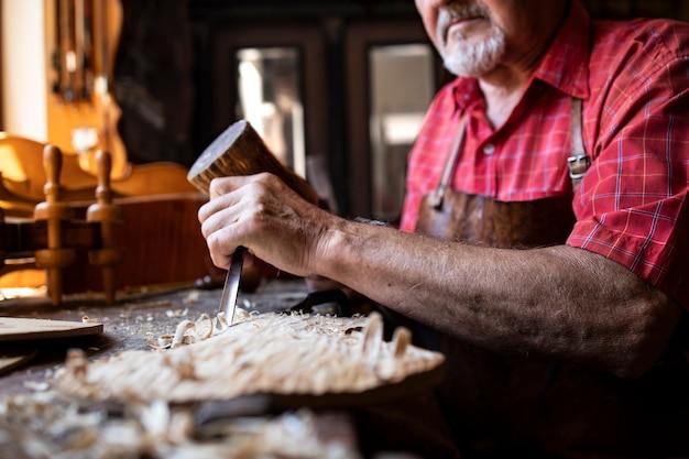 Ein altmodischer erfahrener zimmermann, der in seiner holzbearbeitungswerkstatt messer und hammer hält und holzbrett schnitzt