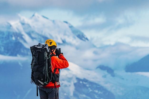 Ein amateur bergsteiger fotograf mit einem großen rucksack