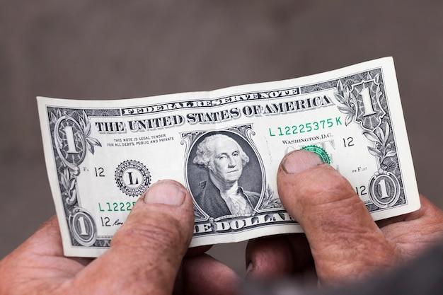 Ein amerikanischer dollar in den händen eines alten mannes, nahaufnahme