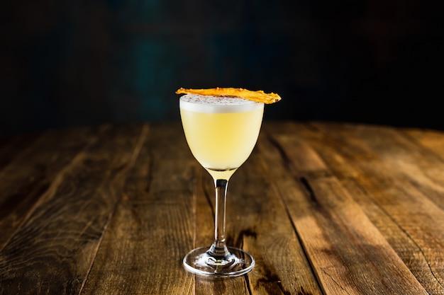 Ein ananas-saurer cocktail in einem nick- und noraglas