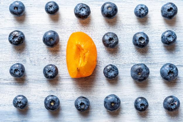 Ein anderes konzept sein. gegen den strich gehen oder sich stromaufwärts bewegen. minimal. gesundes lebensmittelkonzept. sommerfrucht. blaubeer- und aprikosenmuster flach liegen. speicherplatz kopieren. kreatives layout.