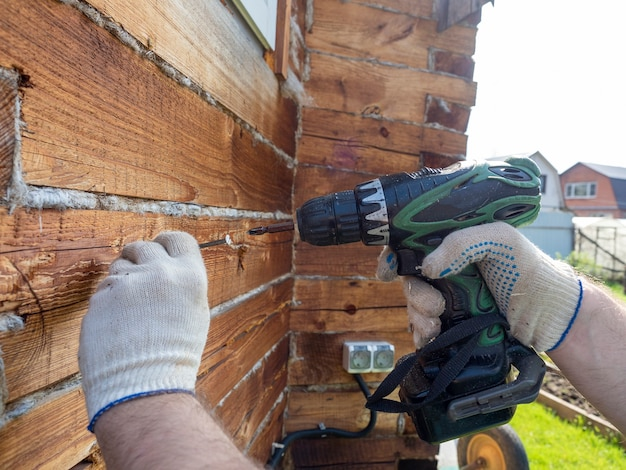 Ein anfänger versucht mit einem elektroschrauber einen nagel in die wand zu schrauben. fehler bei der verwendung von werkzeugen. selektiver fokus