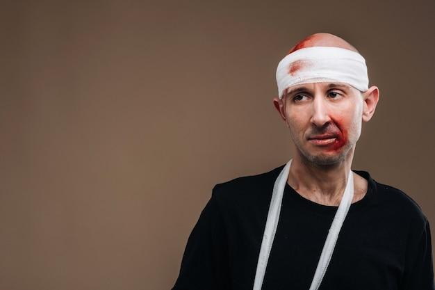 Ein angeschlagener mann mit bandagiertem kopf und gips am arm steht auf grauem grund