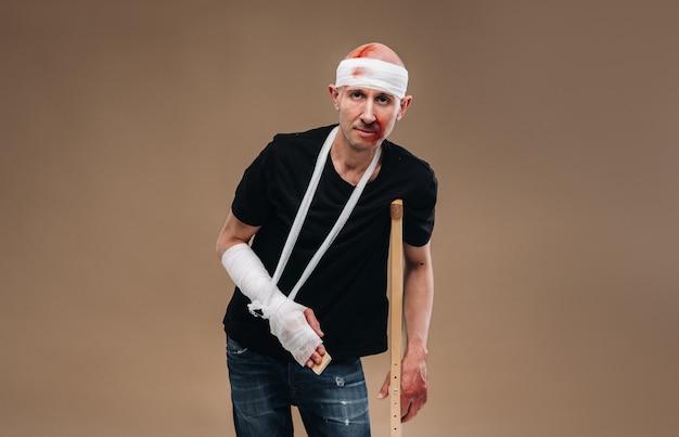 Ein angeschlagener mann mit bandagiertem kopf und gips am arm steht auf krücken auf grauem grund.