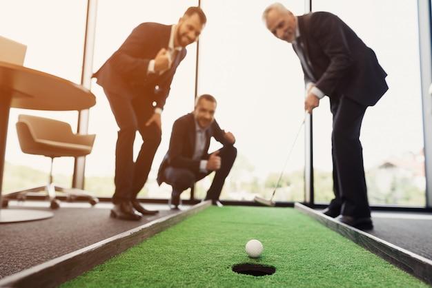Ein angesehener älterer mann spielt in seinem büro golf.