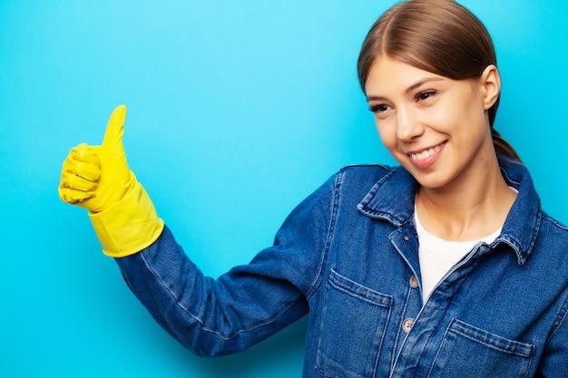 Ein angestellter einer reinigungsfirma in overalls und gelben handschuhen, die auf einem blauen hintergrund aufwerfen