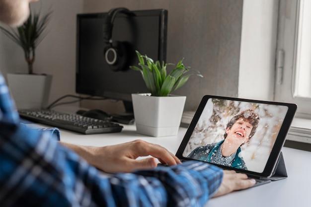 Ein anruf beim freund und ein gespräch über video-chat auf dem tragbaren computergerät.