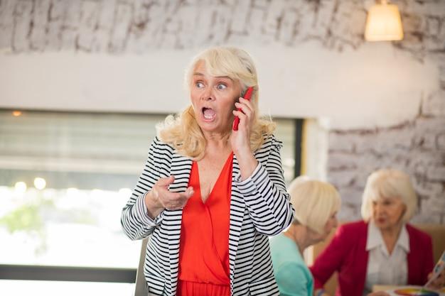 Ein anruf. eine blonde ältere frau, die am telefon spricht und überrascht aussieht