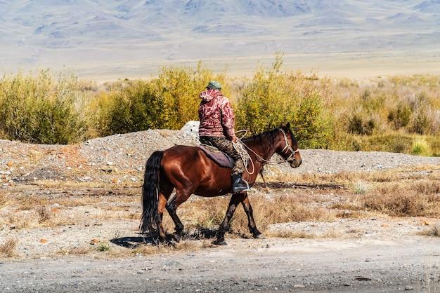 Ein anwohner reitet auf einem pferd im herbstlichen chuy-tal. russland, republik altai