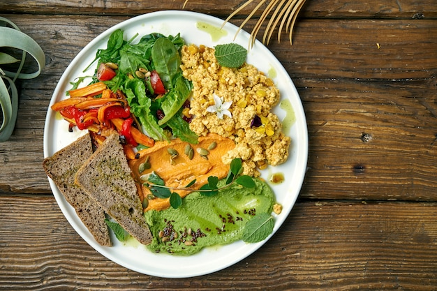 Ein appetitliches vegetarisches gericht besteht aus rührei aus tofukäse, einem salat aus gebackenen paprikaschoten und rucola sowie zwei arten von hummus. holz