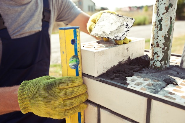 Ein arbeiter baut einen zaunpfosten aus ziegeln