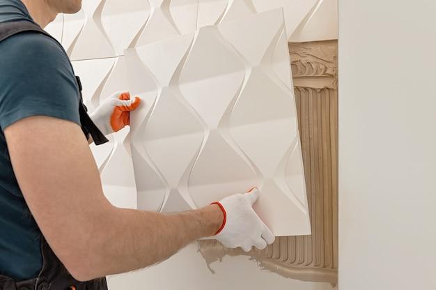 Ein arbeiter befestigt die gipsfliese an der wand