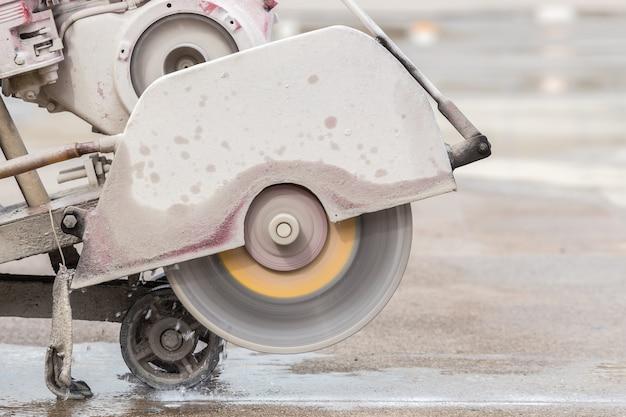 Ein arbeiter, der betonstraße mit diamantsägeblattmaschine schneidet
