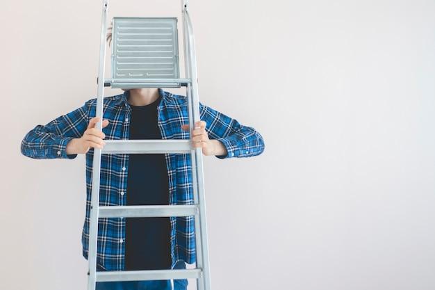 Ein arbeiter, der die aluminiumleiter gegen die wand im neuen haus hält
