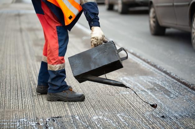 Ein arbeiter gießt flüssigen asphalt, geschmolzenes bitumen aus einem eimer harz.